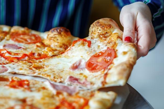Un morceau de pizza délicieuse sur la table. Photo Premium