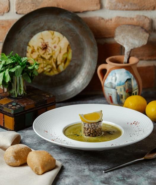 Un morceau rond de nourriture russe traditionnelle avec une sauce grasse et une tranche de citron sur le dessus Photo gratuit
