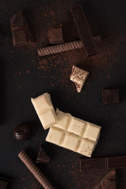 Morceaux De Barre De Chocolat Et Bonbons Sur La Surface En Bois Photo gratuit