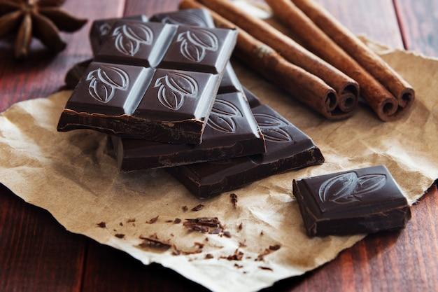 Morceaux de chocolat et de la cannelle sur fond en bois Photo Premium