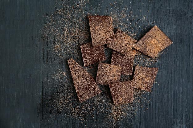 Morceaux de chocolat cassé et poudre de cacao sur fond noir. copiez l'espace. Photo Premium
