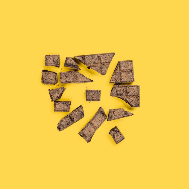 Des Morceaux De Chocolat écrasés Sur Une Surface Jaune Photo gratuit