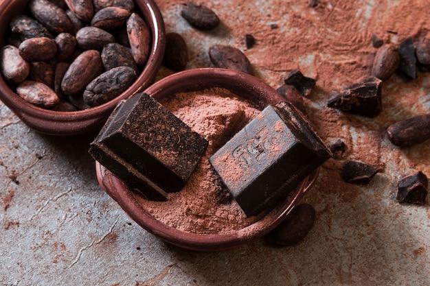 Morceaux de chocolat sur la poudre de cacao et les haricots sur la table Photo gratuit
