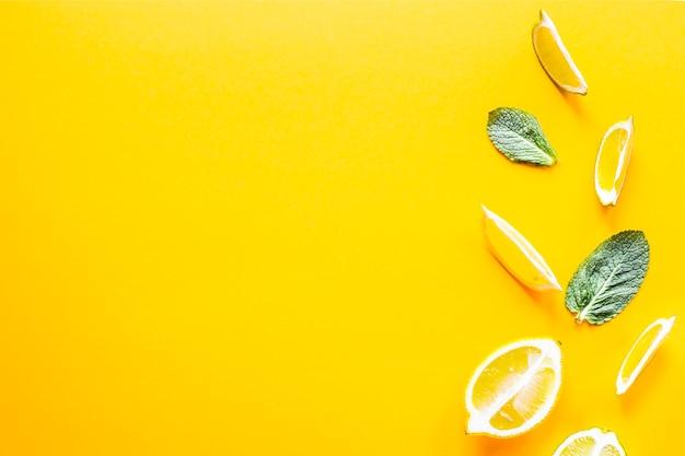 Morceaux de citron, citron vert et menthe verte sur fond jaune Photo Premium