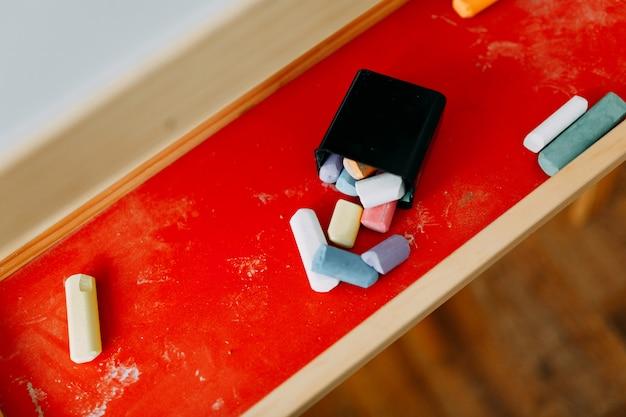 Des morceaux colorés de craie reposent sur un pied rouge pour des planches à dessin et un bazar créatif Photo Premium