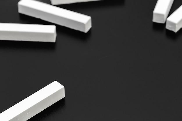 Morceaux de craie blanche photographiés sur un tableau noir Photo Premium