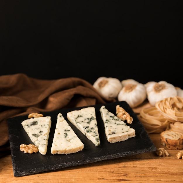 Morceaux de fromage gorgonzola sur pierre noire avec noix et ail sur le bureau Photo gratuit