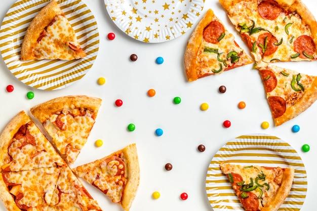 Morceaux De Pizza Et Bonbons Colorés Sur Fond Blanc. Anniversaire Avec De La Malbouffe. Fête Des Enfants. Vue De Dessus Avec Espace De Copie Pour Le Texte. Mise à Plat Photo Premium