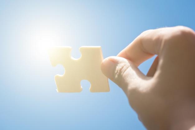 Morceaux de puzzle dans les mains de la femme avec fond de ciel bleu Photo Premium