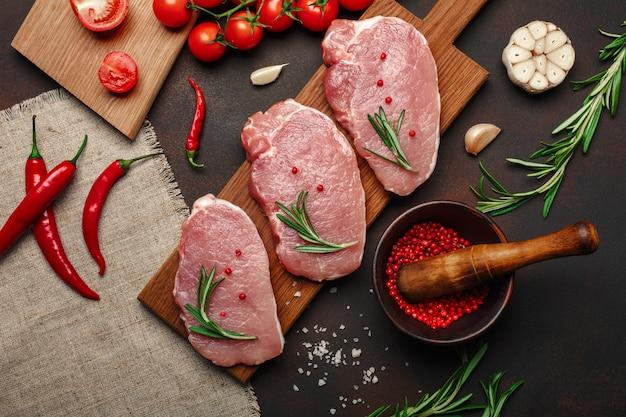 Morceaux de steak de porc cru sur une planche à découper avec mortier aux tomates cerises, romarin, ail, poivre, sel et épices Photo Premium