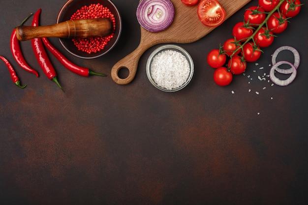 Morceaux de steak de porc cru sur une planche à découper avec tomates cerises, romarin, ail, poivron rouge, laurier, oignon Photo Premium