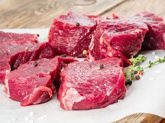 Morceaux de striploin brut. bœuf cru aux épices sur papier sulfurisé sur fond en bois Photo Premium