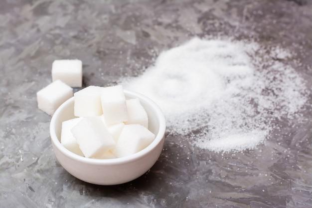 Morceaux de sucre raffiné dans un bol et un tas de sable sucré sur la table Photo Premium