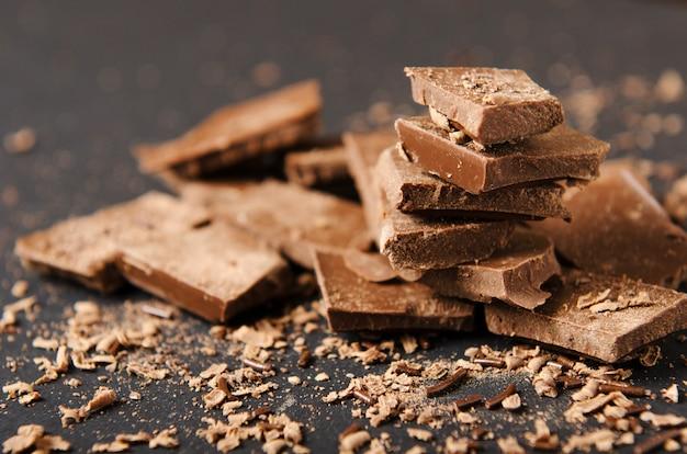 Morceaux De Tablette De Chocolat Empilés Avec Des Pépites De Chocolat Sur Un Fond Noir Photo Premium