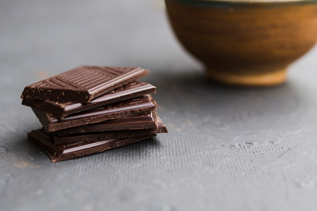 Morceaux de tablettes de chocolat brisées sur une table grise Photo gratuit