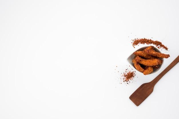 Morceaux de viande frits avec des épices et une spatule sur table grise Photo gratuit