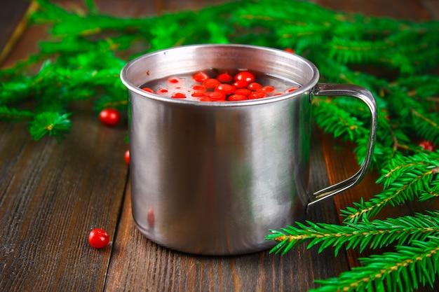 Morse ou thé de myrtille dans une tasse en étain, entourée de branches de sapin sur une table en bois. Photo Premium