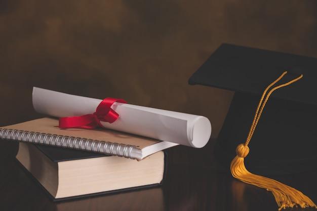 Un mortier de graduation sur une pile de livres, avec un parchemin noué dans le ruban rouge. Photo Premium