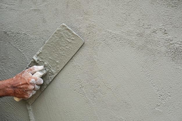 Mortier de lissage main-constructeur main appliquée sur le mur Photo Premium
