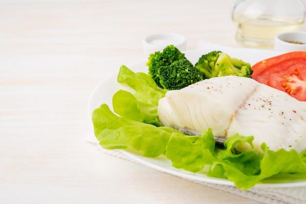 Morue à la vapeur. paléo, céto, fodmap alimentation saine avec des légumes sur une plaque blanche Photo Premium