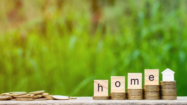 Mot d'accueil sur la pile de pièces et un tas de pièces d'or sur la table en bois. Photo Premium