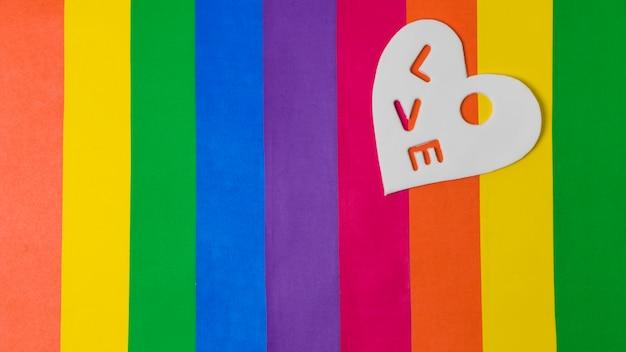 Mot d'amour sur le coeur au-dessus du drapeau lgbt Photo gratuit