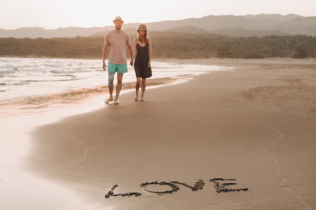 Mot amour sur la côte de sable et floue couple d'amoureux sur fond marchant Photo gratuit