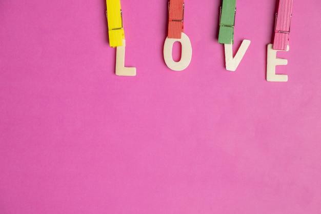 Mot amour dans les coeurs rouges sur fond rose, icône de l'amour, saint valentin, concept de relations Photo Premium