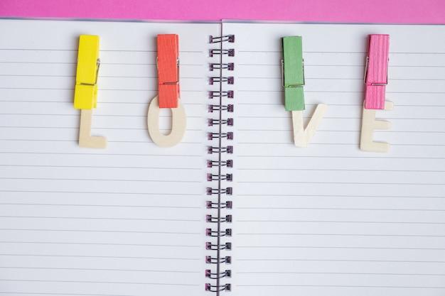 Mot amour dans un livre blanc sur fond rose avec un espace pour le texte Photo Premium