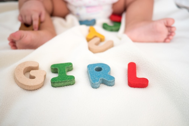 Mot en bois fille texte sur couverture avec pied de l'enfant et copie espace arrière-plan Photo Premium