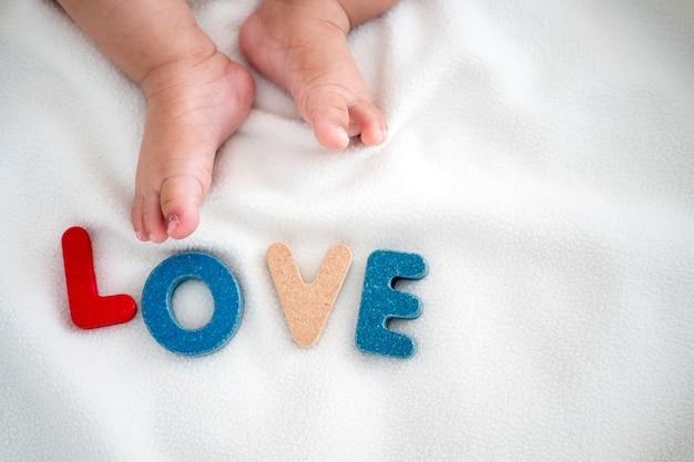 Mot en bois de texte d'amour sur la couverture avec le pied de l'enfant et l'arrière-plan de l'espace copie Photo Premium