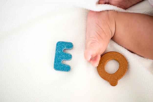 Mot en bois texte eq sur couverture avec pied enfant flou et fond de copie espace Photo Premium