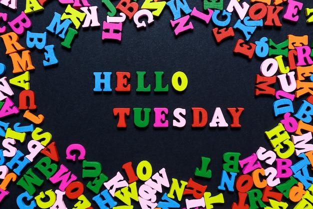 Le mot bonjour mardi de lettres en bois multicolores sur fond noir Photo Premium