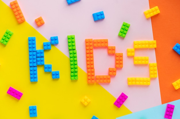 Mot d'épeautre pour enfants avec fond de blocs en plastique Photo gratuit