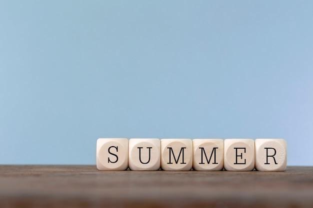 Mot de l'été écrit en cube de bois sur une table en bois Photo Premium