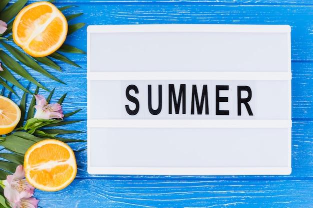 Mot de l'été sur tablette près de la plante laisse avec des oranges fraîches Photo gratuit