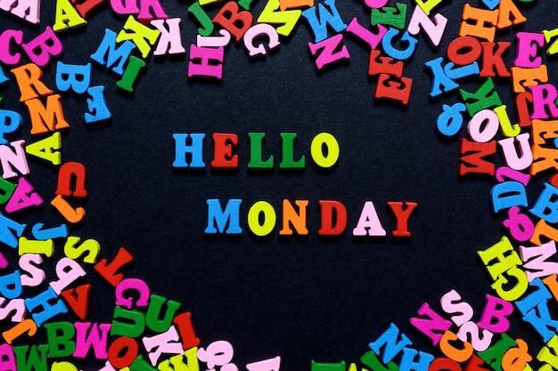 Le mot hello monday à partir de lettres en bois multicolores sur fond noir Photo Premium