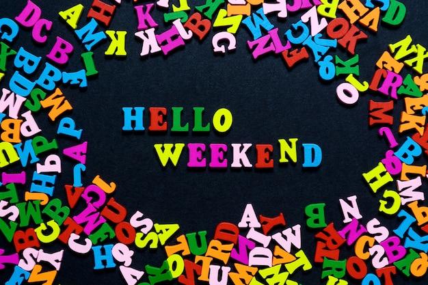 Le mot hello weekend de lettres en bois multicolores sur fond noir Photo Premium