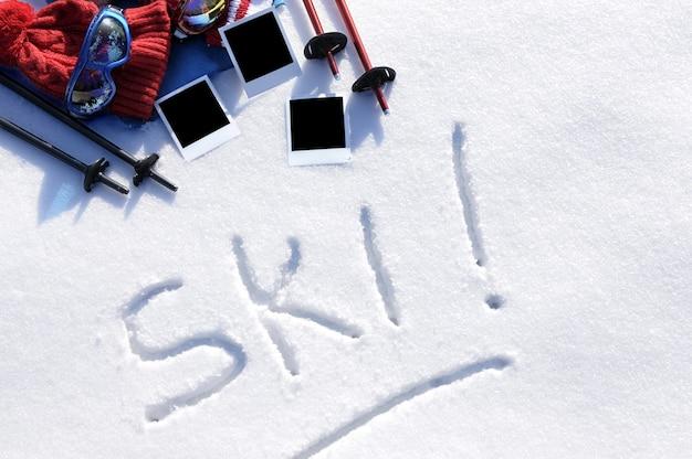 Le mot ski écrit dans la neige avec des bâtons de ski, des lunettes et des chapeaux et des tirages photo vierges Photo Premium