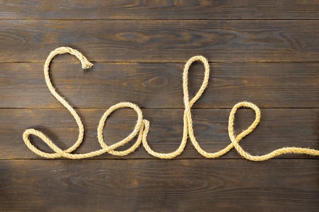 Mot vente est écrit d'une corde de jute brute sous la forme d'une pièce reposant sur une planche de bois texturée brune Photo Premium