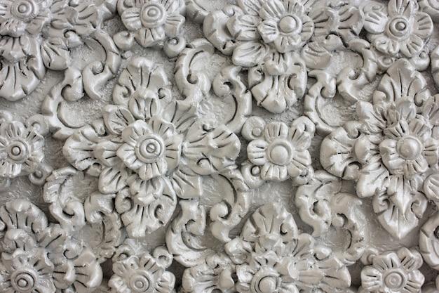 Motif de fleur gris sculpté sur la conception en stuc du mur natal Photo Premium