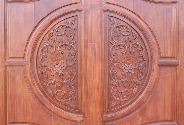 Motif de fleur sculpté sur fond de bois. style thaï traditionnel en bois Photo Premium