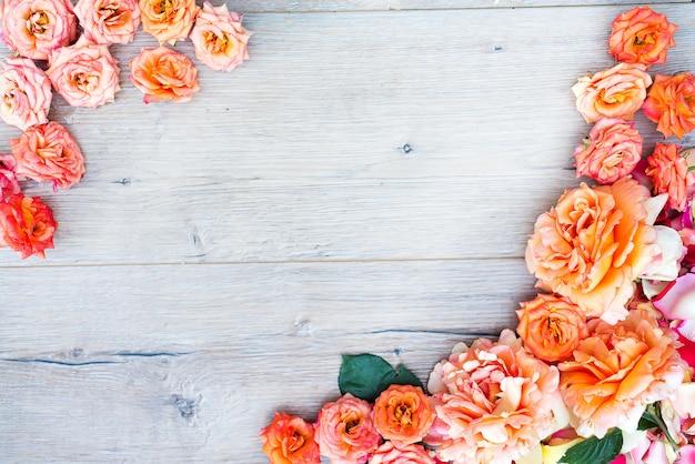 Motif floral, cadre composé de roses sur fond en bois. lay plat, vue de dessus. Photo Premium