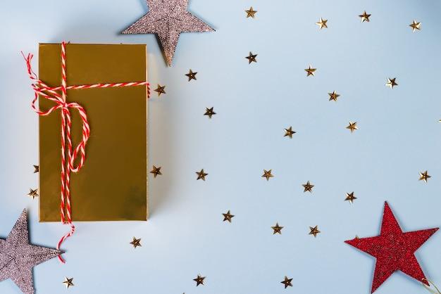 Motif De Noël En étoiles Dorées, Argentées Et Rouges Avec Un Coffret Doré Sur Bleu Photo Premium