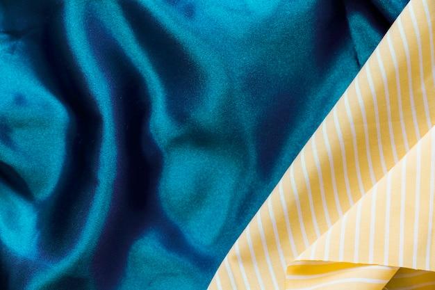 Motif de rayures jaunes sur fond textile bleu uni Photo gratuit
