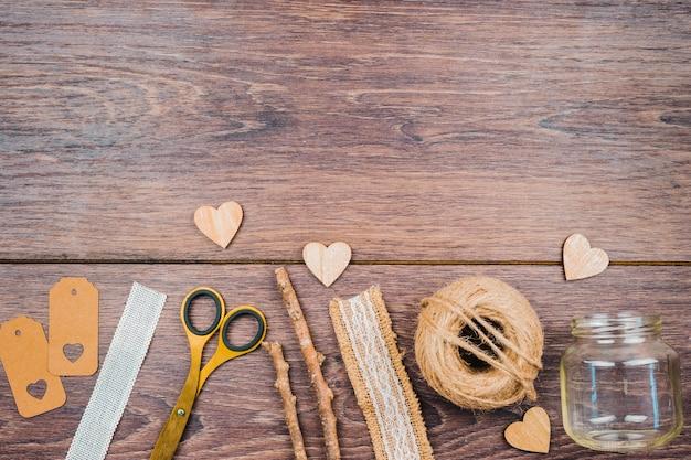 Mots Clés; Règle; Ciseaux; Des Bâtons; Ruban De Dentelle; Pot Vide Et Forme De Coeur Sur Fond En Bois Photo gratuit
