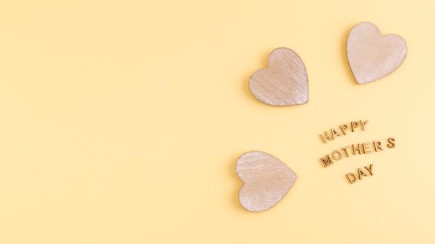 Mots de fête des mères heureux et coeurs en bois Photo gratuit
