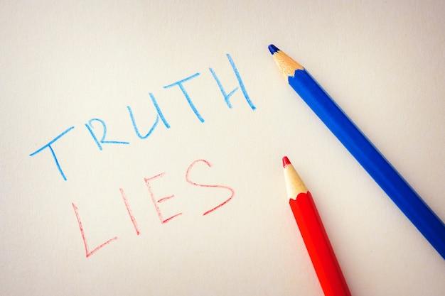 Les mots vérité et mensonges sont écrits sur papier Photo Premium