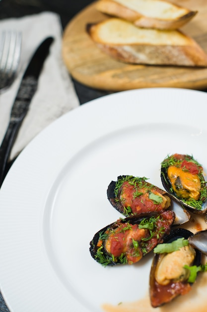 Moules au four à la sauce tomate avec coriandre et parmesan sur une assiette blanche. Photo Premium