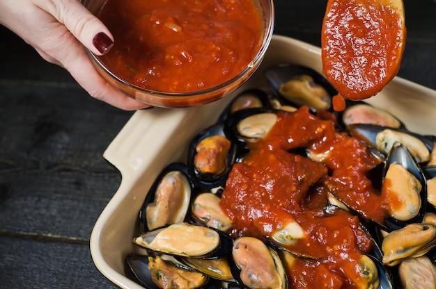 Moules crues à la pâte de tomates, cuisson. Photo Premium